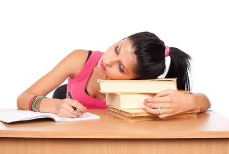 Portrait of a cute teenage girl sleeping on a stack of books at her desk Stock Photo - 7316792
