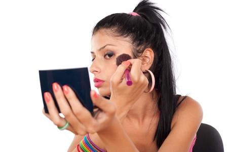 Close up of a beautiful brunette woman applying makeup photo