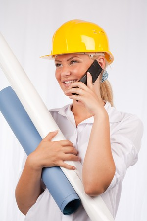 Portrait of a beautiful engineer woman with yellow hard hat holding technical papers or plans photo