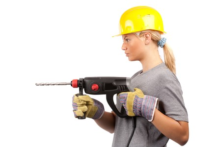 Attractive young lady worker with a pneumatic drilling machine isolated on white photo