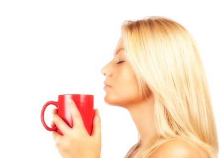 Close up portrait of an attractive blonde lady drinking coffee or tea photo