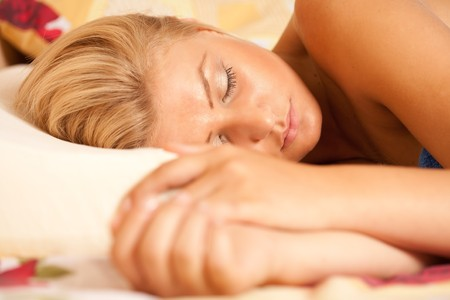 Close up portrait of a beautiful young blonde woman sleeping in her bed photo