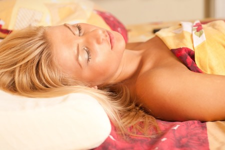 Close up portrait of a beautiful young blonde woman sleeping in her bed Stock Photo - 7365853