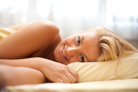 Close up portrait of a beautiful blonde woman preparing to sleep (or just awaken in the morning) Stock Photo - 7365831