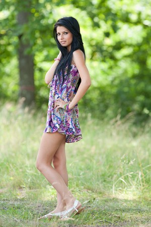 Full length portrait of a beautiful brunette woman outdoor photo