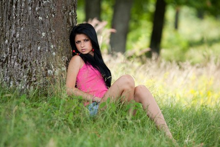 face in tree bark: Attractive brunette lady sitting near a tree