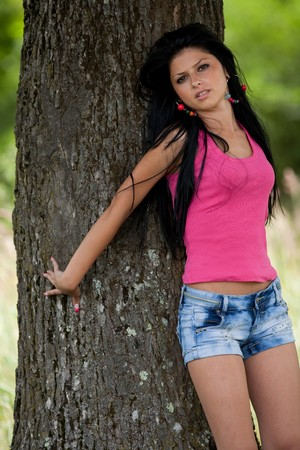 face in tree bark: Beautiful brunette lady leaning against a tree in the forest Stock Photo