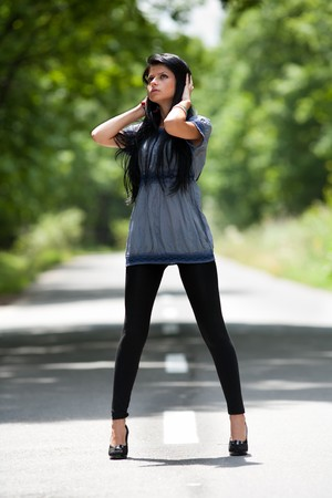 Full body portrait of a young lady standing in the road photo