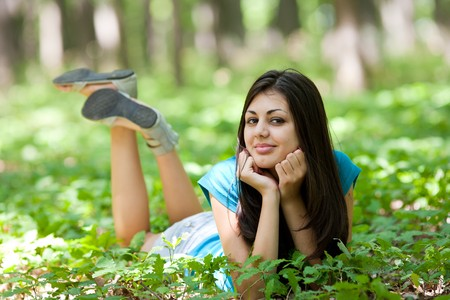lying in leaves: Portrait of a beautiful brunette woman lying in the forest Stock Photo