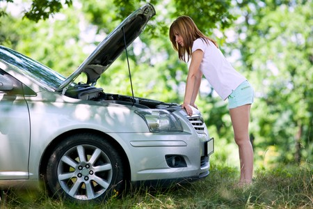 Young woman with a broken car in a forest trying to fix it Stock Photo - 7461473