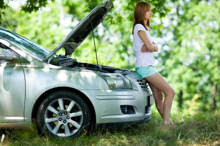 Young woman with a broken car in a forest waiting for service photo