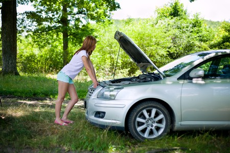 Young woman with a broken car in a forest trying to fix it Stock Photo - 7461500