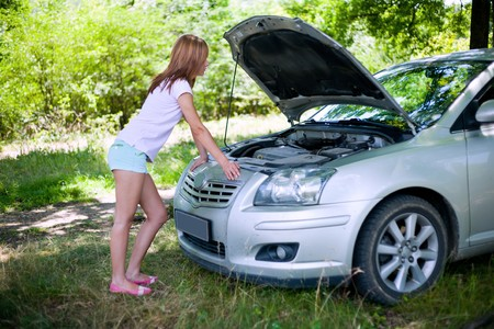 Young woman with a broken car in a forest trying to fix it photo