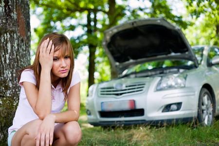 broken car: Mujer molesta con un coche roto en un bosque a la espera de ayuda