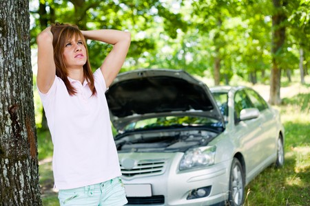 Desperate woman with a broken car in a forest waiting for help photo