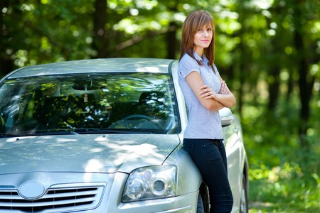 Business woman standing near by her car in a forest photo