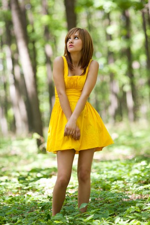 Scared blonde woman in yellow dress in the forest photo