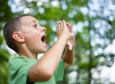 Close up portrait of a kid yelling into the forest photo