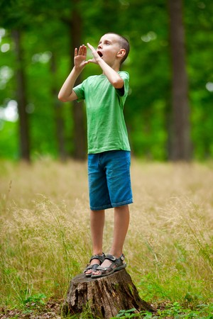 call of nature: Cute little kid trying to make echo in the forest by shouting
