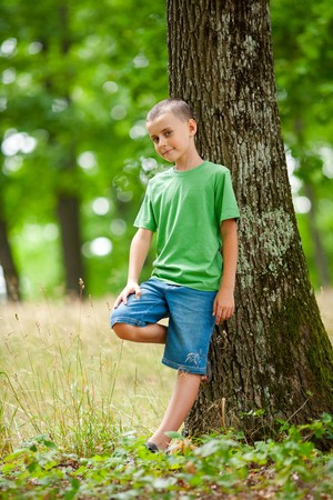 Portrait of a kid in the forest, leaning against a tree photo