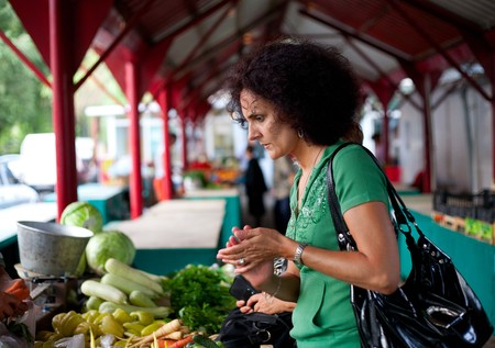 Young woman buying fresh vegetables at the farmers market photo