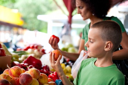 farmers' market: Cute boy with his mother buying fresh vegetables at the farmers market