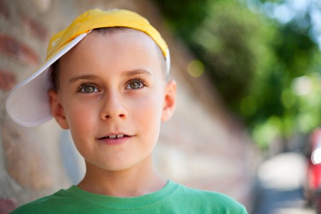 Close up portrait of a beautiful child leaning on an old brick wall photo