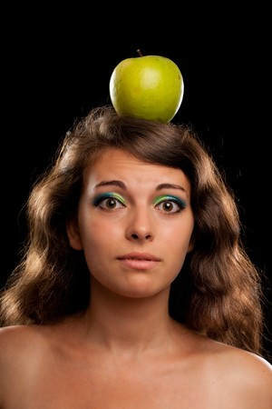 Portrait of a woman holding an apple on her head, isolated on black background photo
