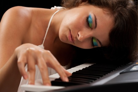 Close up of a beautiful young woman playing piano photo