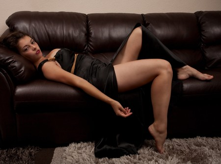 Beautiful young woman in black dress lying on a leather couch photo