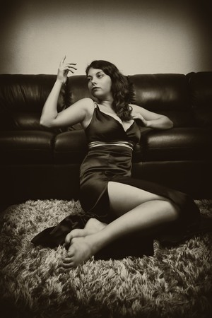 Vintage sepia stylized portrait of a beautiful woman near a couch photo
