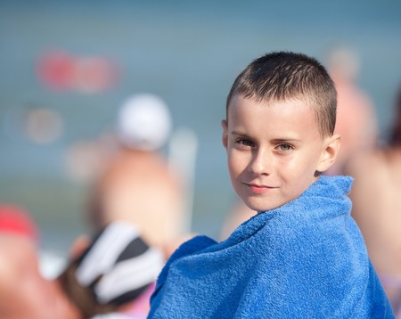 Cute kid wrapped in a blue towel sitting on the beach in the sun photo