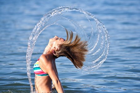 Motion freeze on a girl splashing the sea water with her hair photo