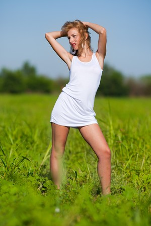 Beautiful young woman in white dress on a meadow photo