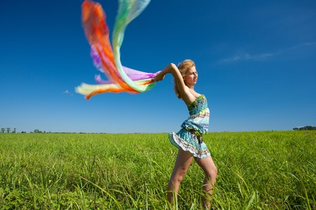 Beautiful blonde woman with colorful scarf in the wind, motion blur photo