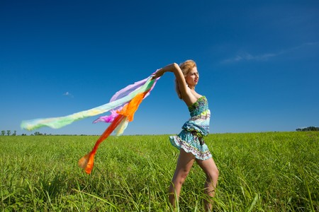 Beautiful blonde woman with colorful scarf in the wind, motion blur Stock Photo