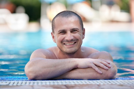 hispanic: Young man smiling happy to the edge of a pool with clear blue water