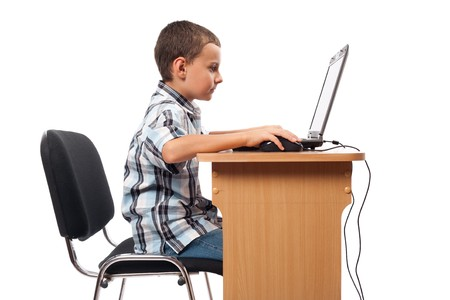 Cute schoolboy sitting at his laptop doing homework or playing, isolated on white background Stock Photo