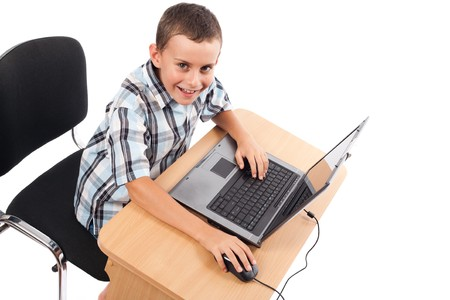 Cute schoolboy sitting at his laptop doing homework or playing, isolated on white background Stock Photo - 7730276