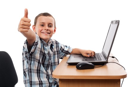 Cute schoolboy sitting at his laptop doing homework or playing, isolated on white background Stock Photo - 7730252