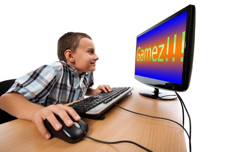 computer game: Schoolboy happy to play games at his computer instead of doing homework Stock Photo