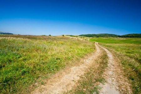 Dirty rural road in countryside, going over hills Stock Photo - 7730495