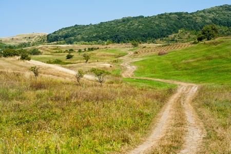 Dirty rural road in countryside, going over hills photo
