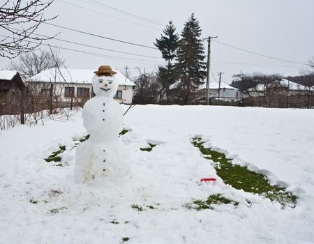 Snowman built in the countryside in a cloudy day photo