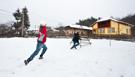 Young couple having fun with a snowball fight photo