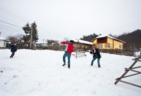 Young family having fun with a snowball fight during winter holiday photo