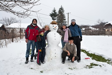 Multi generation family gathering happily together around a snowman, in winter holiday photo