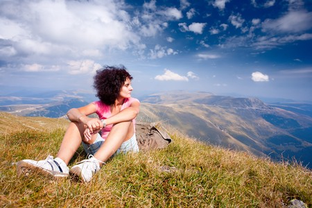 Attractive young woman hiking into a beautiful alpine landscape photo