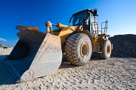 Bulldozer or excavator, industrial machinery against the blue sky Stock Photo - 7730999