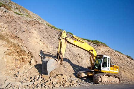 Bulldozer or excavator, industrial machinery against the blue sky Stock Photo - 7731005
